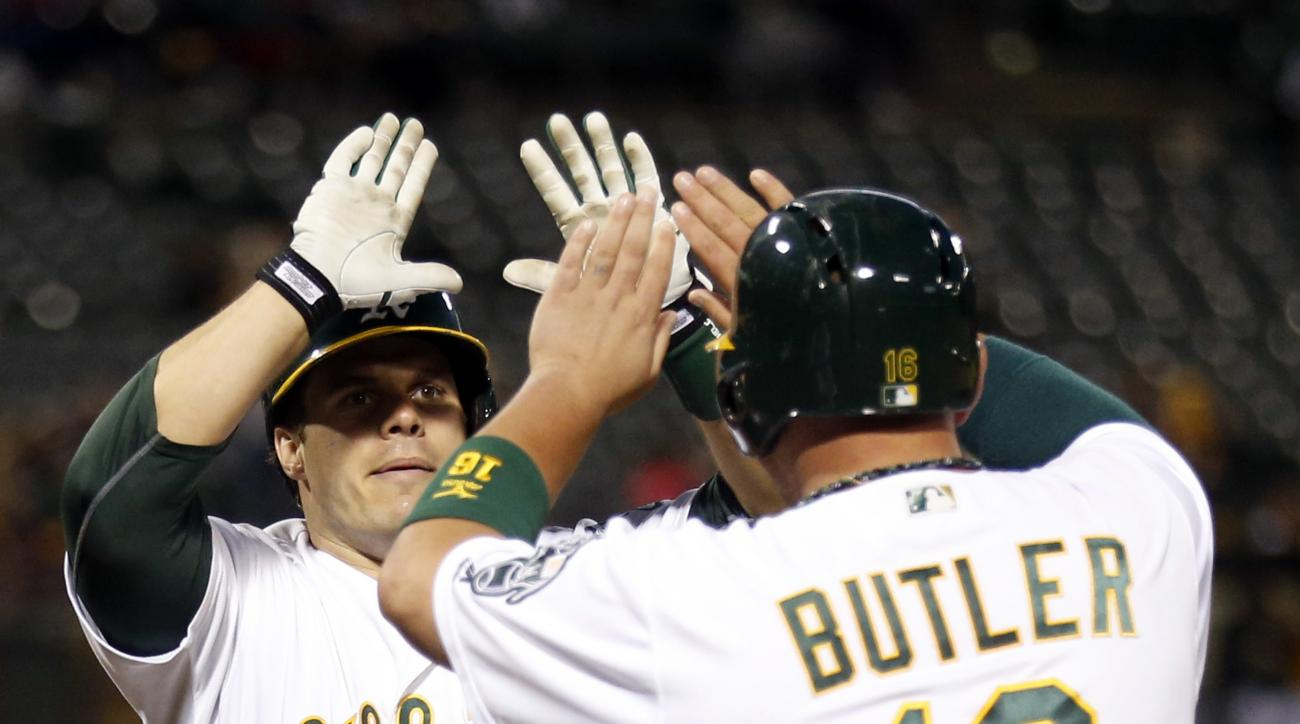 Oakland Athletics' Josh Phegley (19) celebrates his three-run home run off Texas Rangers' Tom Wilhelmsen with teammate Billy Butler (16) during the fourth inning of a baseball game Monday, June 13, 2016, in Oakland, Calif. (AP Photo/D. Ross Cameron)