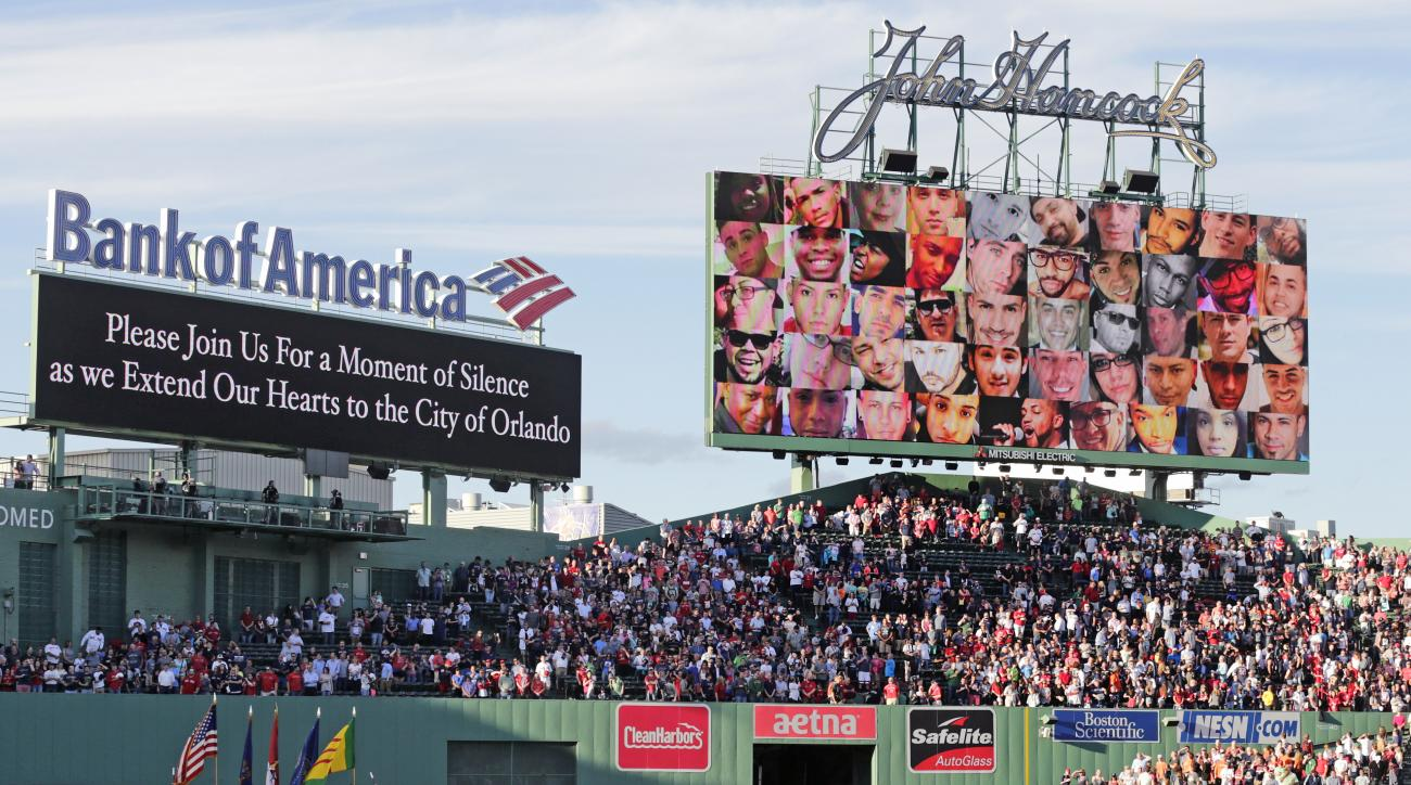 Photographs of victims from the Orlando night club shooting are displayed as fans pause for a moment of silence prior to the first inning of a baseball game between the Baltimore Orioles and Boston Red Sox at Fenway Park, Tuesday, June 14, 2016, in Boston
