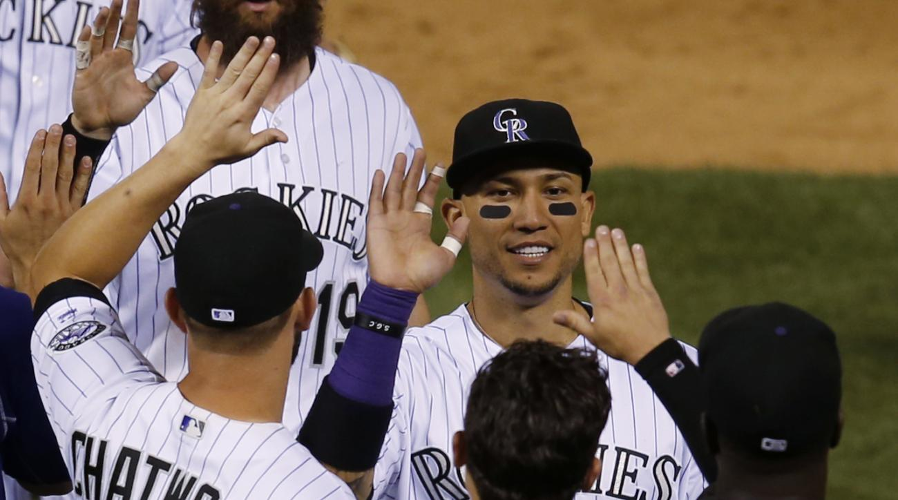 Colorado Rockies right fielder Carlos Gonzalez, facing camera, is congratulated by teammates the Rockies defeated the New York Yankees 13-10 in a baseball game Tuesday, June 14, 2016, in Denver.  (AP Photo/David Zalubowski)