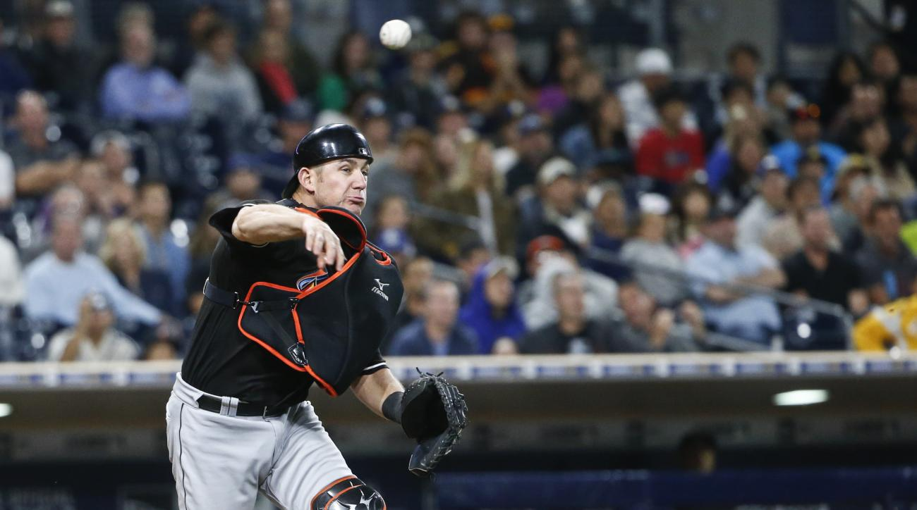 Miami Marlins catcher Jeff Mathis throws to first to put out San Diego Padres' Jon Jay after a third strike got away from Mathis with a runner on third during the seventh inning of a baseball game Tuesday, June 14, 2016, in San Diego. (AP Photo/Lenny Igne