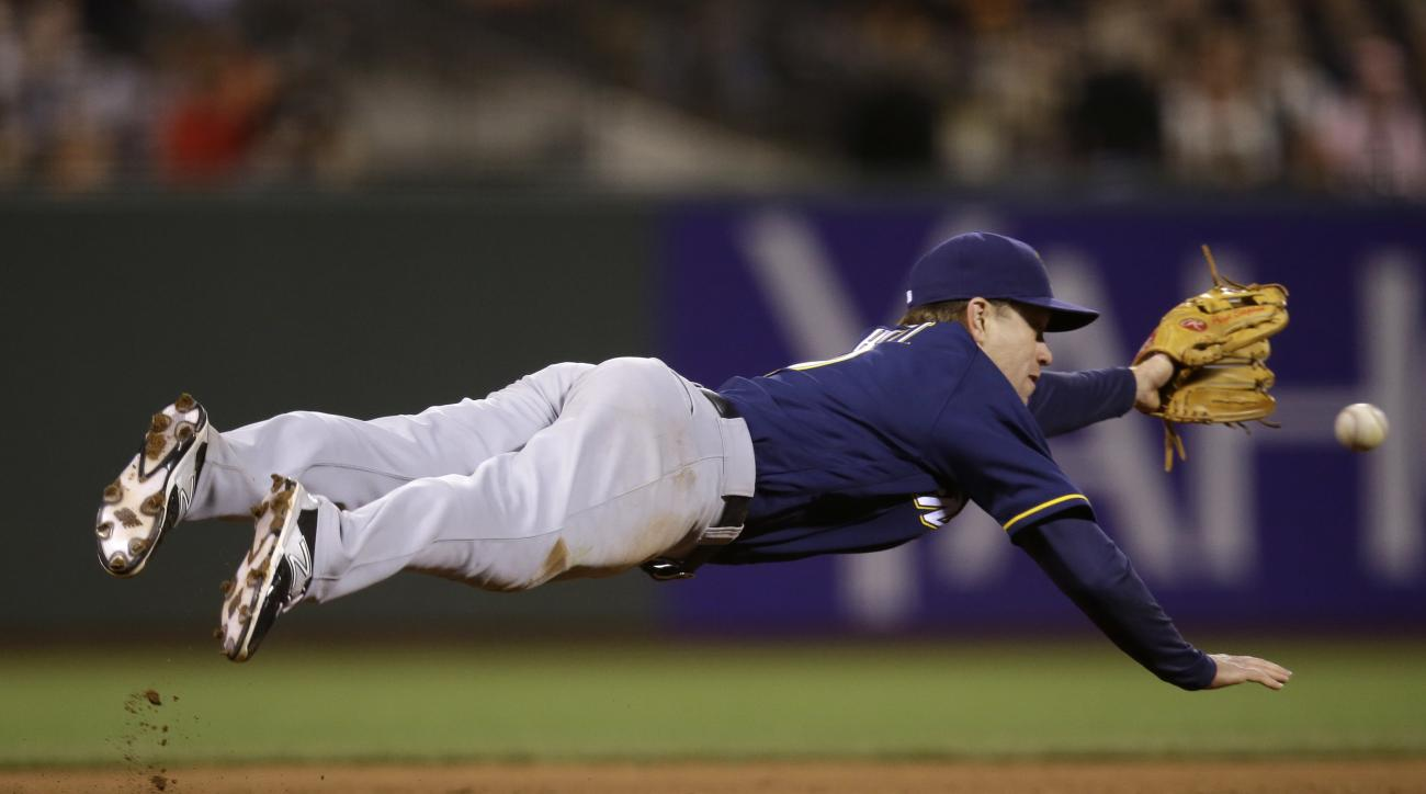 Milwaukee Brewers third baseman Aaron Hill makes a diving attempt at a ground ball from San Francisco Giants' Buster Posey during the fifth inning of a baseball game Tuesday, June 14, 2016, in San Francisco. Posey singled on the play. (AP Photo/Marcio Jos