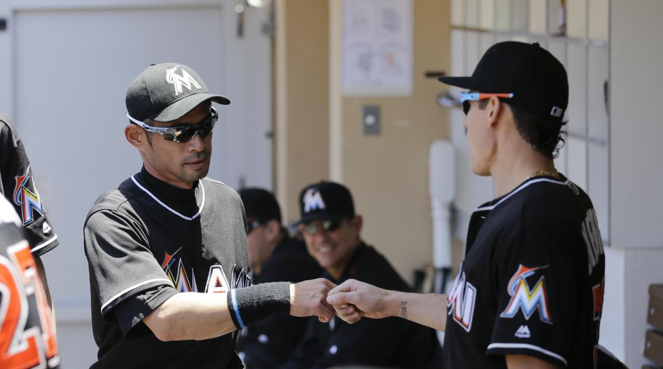 Miami Marlins' Ichiro Suzuki, left, is greeted at the dugout by second baseman Derek Dietrich after scoring off an RBI single by Christian Yelich during the first inning of a baseball game against the San Diego Padres Wednesday, June 15, 2016, in San Dieg