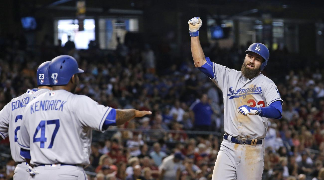 Los Angeles Dodgers' Scott Van Slyke, right, celebrates his three-run home run against the Arizona Diamondbacks with Howie Kendrick (47) and Adrian Gonzalez, left, during the sixth inning of a baseball game Wednesday, June 15, 2016, in Phoenix. (AP Photo/