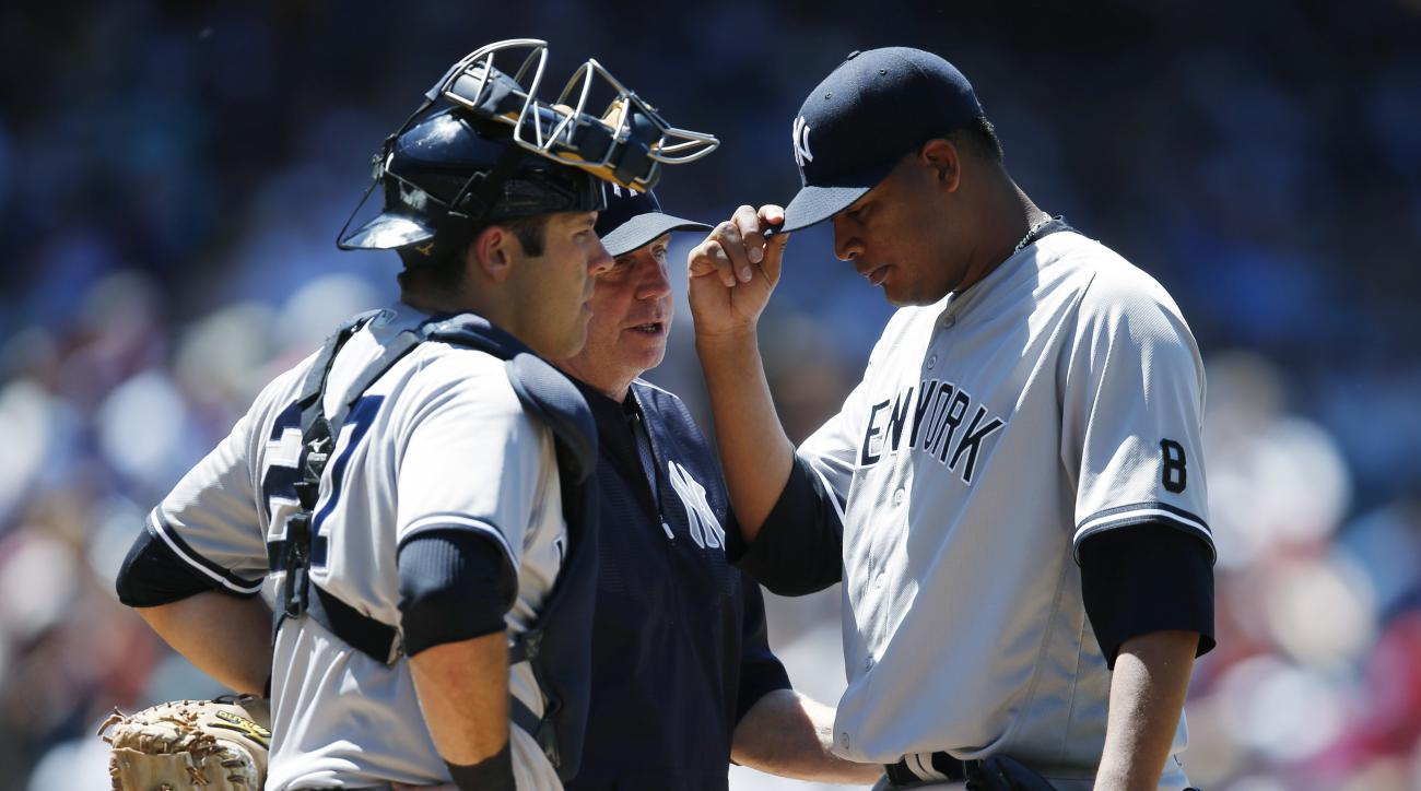 New York Yankees starting pitcher Ivan Nova, right, adjusts his cap as he confers with pitching coach Larry Rothschild, center, and catcher Austin Romine after Nova gave up a double to Colorado Rockies' Trevor Story in the fifth inning of a baseball game