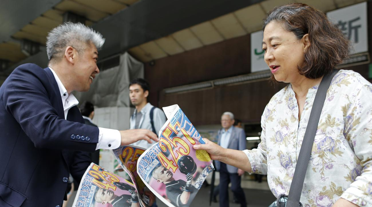 An extra of a Japanese sports newspaper reporting Miami Marlins' Ichiro Suzuki's 4,257th hit, is handed over to a pedestrian in Tokyo, Thursday, June 16, 2016. Suzuki raised his career total in the Japanese and North American major leagues to 4,257, passi