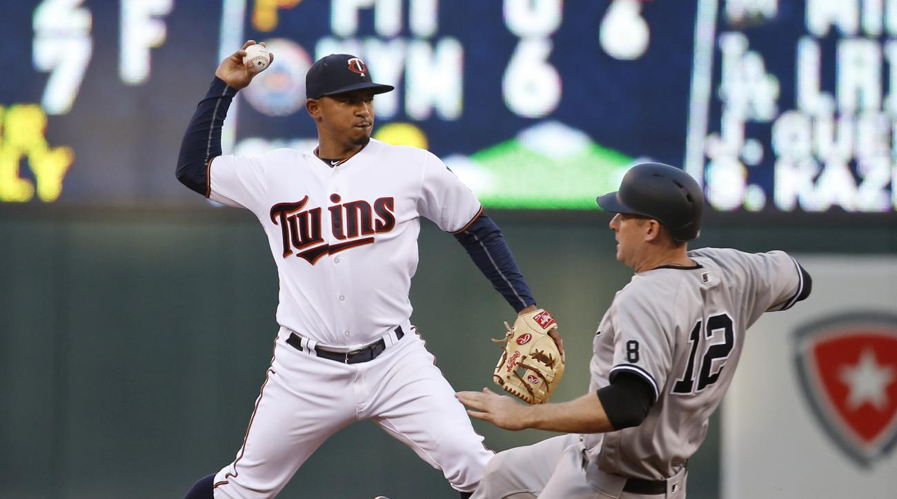 Minnesota Twins shortstop Eduardo Escobar, left, makes the throw to first to turn a double play after forcing out New York Yankees' Chase Headley (12) at second base during the third inning of a baseball game in Minneapolis, Thursday, June 16, 2016. The Y