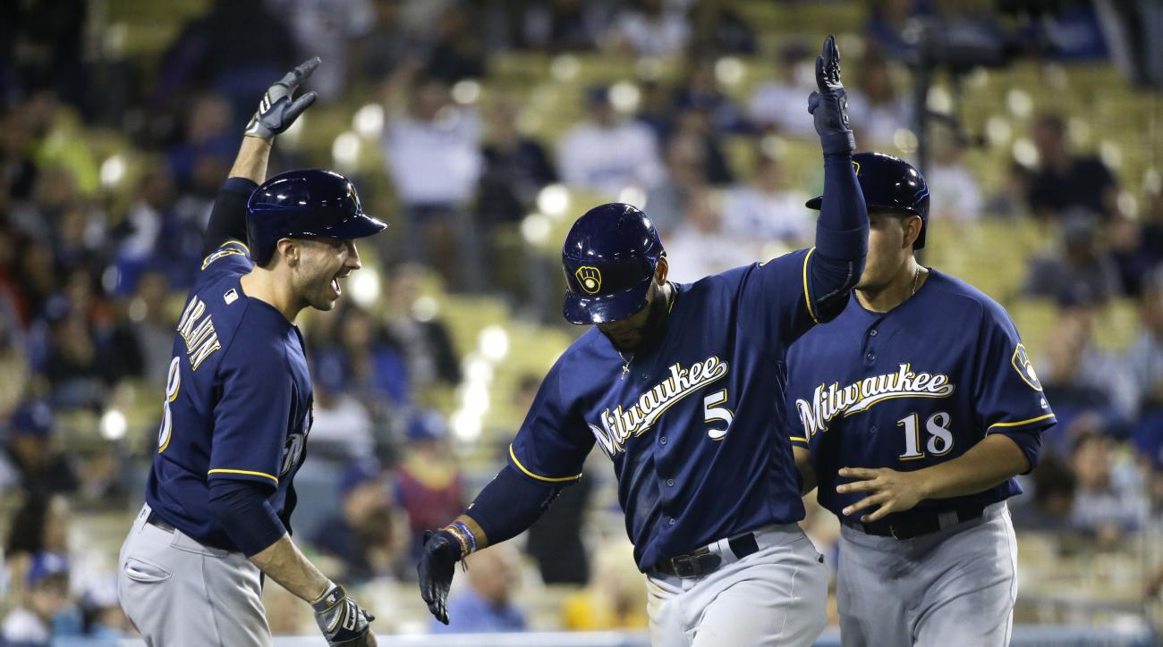 Milwaukee Brewers' Jonathan Villar, center, celebrates his two-run home run with Ryan Braun, left, and Ramon Flores during the ninth inning of a baseball game against the Los Angeles Dodgers, Thursday, June 16, 2016, in Los Angeles. (AP Photo/Jae C. Hong)