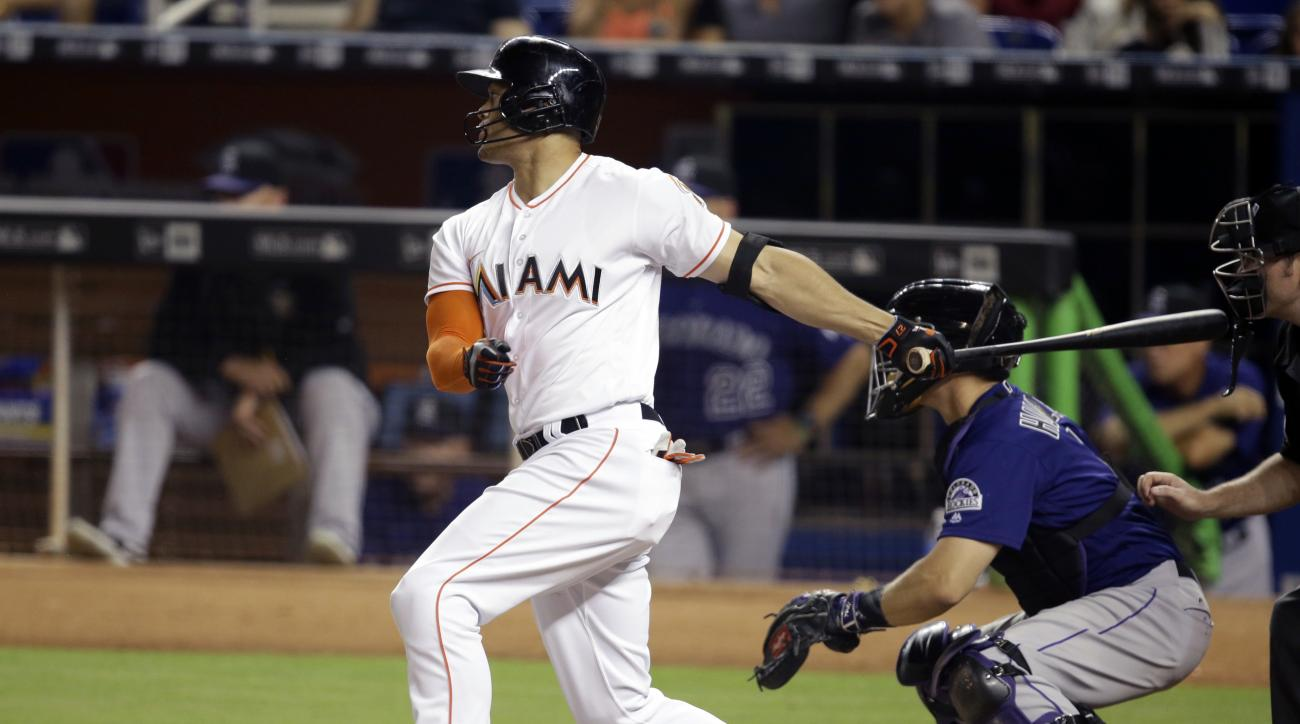 Miami Marlins' Giancarlo Stanton, left, watches after hitting a single during the fourth inning of a baseball game against the Colorado Rockies, Friday, June 17, 2016, in Miami. Rockies catcher Nick Hundley, second from right, looks on. (AP Photo/Lynne Sl