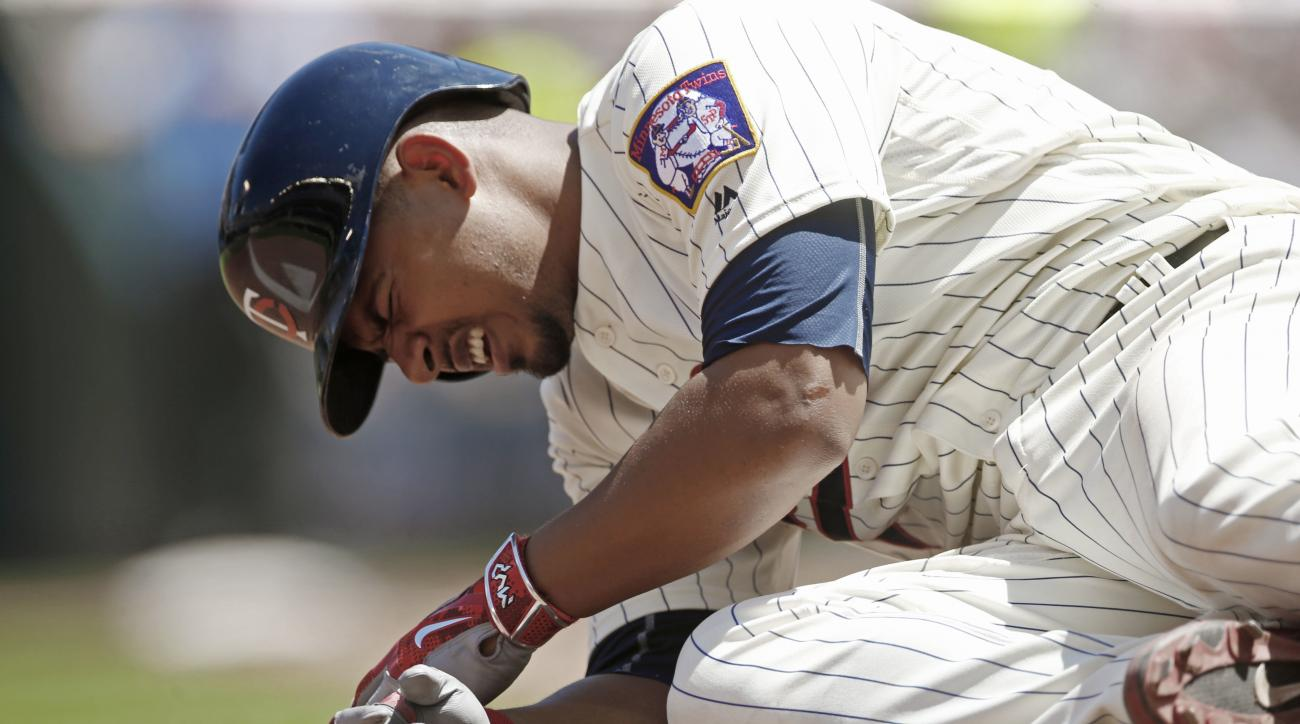 Minnesota Twins' Eduardo Escobar grimaces after fouling the ball off his foot on a pitch by New York Yankees' Michael Pineda in the fourth inning of a baseball game Saturday, June 18, 2016, in Minneapolis. (AP Photo/Jim Mone)