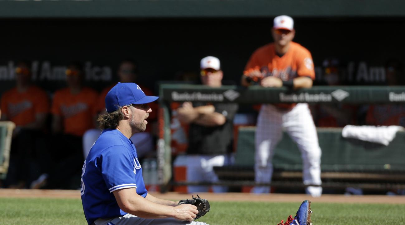 Toronto Blue Jays starting pitcher R.A. Dickey sits on the ground after not being able to tag out Manny Machado as he scored on a passed ball in the first inning of a baseball game in Baltimore, Saturday, June 18, 2016. (AP Photo/Patrick Semansky)
