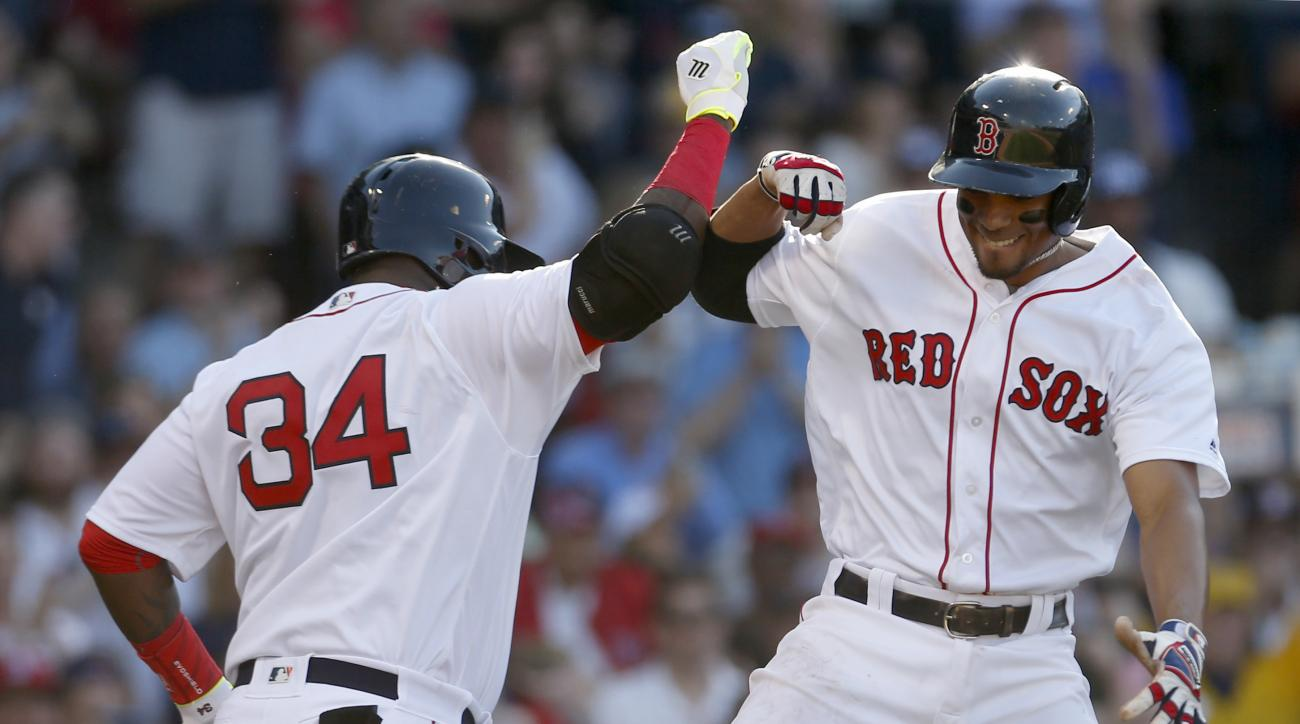 Boston Red Sox's Xander Bogaerts, right, leaps to celebrate with on deck batter David Ortiz after hitting a home run during the fifth inning of a baseball game against the Seattle Mariners at Fenway Park, Saturday, June 18, 2016, in Boston. (AP Photo/Mary