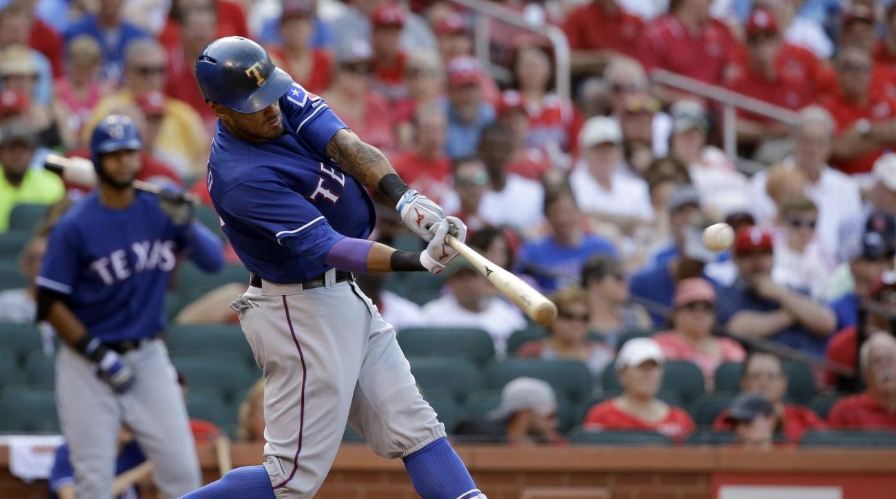 Texas Rangers' Ian Desmond hits a sacrifice fly to score Jurickson Profar during the ninth inning of a baseball game against the St. Louis Cardinals, Saturday, June 18, 2016, in St. Louis. (AP Photo/Jeff Roberson)