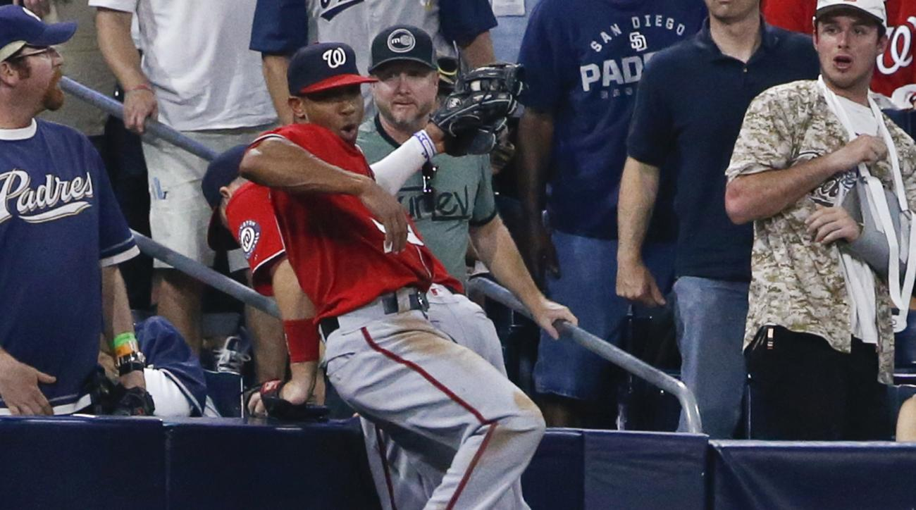 Washington Nationals left fielder Ben Revere spins off third baseman Stephen Drew while catching a pop foul hit by San Diego Padres' Brett Wallace during the sixth inning of a baseball game Saturday, June 18, 2016, in San Diego. (AP Photo/Lenny Ignelzi)
