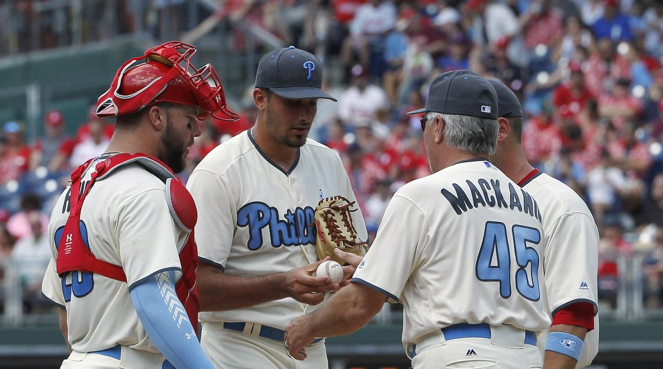 Philadelphia Phillies staring pitcher Zach Elfin, center, hands the ball to manager Pete Mackanin, front right, as he leaves a baseball game during the sixth inning against the Arizona Diamondbacks, Sunday, June 19, 2016, in Philadelphia. (AP Photo/Tom Mi