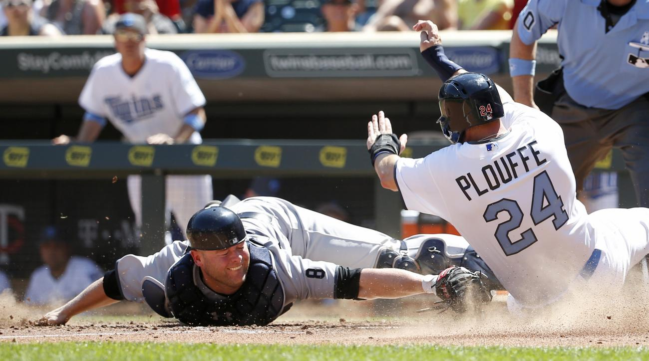 Minnesota Twins' Trevor Plouffe (24) is safe at home plate as he avoids the tag of New York Yankees catcher Brian McCann on a two-run triple by Twins' Eduardo Escobar during the sixth inning of a baseball game in Minneapolis, Sunday, June 19, 2016. (AP Ph
