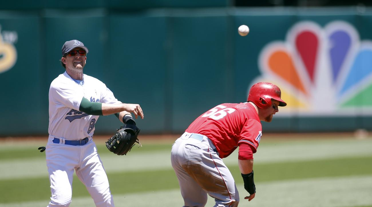 Oakland Athletics second baseman Jed Lowrie (8) throws over Los Angeles Angels' Kole Calhoun too late to double up Albert Pujols at first during the first inning of a baseball game Sunday, June 19, 2016, in Oakland, Calif. (AP Photo/D. Ross Cameron)