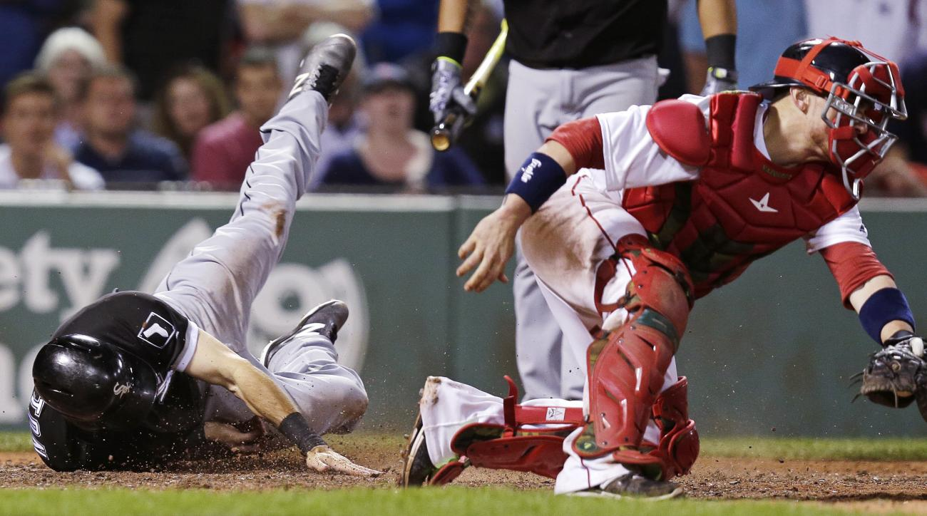 Chicago White Sox's Adam Eaton, left, touches home plate as he slides past Boston Red Sox catcher Christian Vazquez while scoring on a two-run double by Jose Abreu in the 10th inning of a baseball game at Fenway Park, Monday, June 20, 2016, in Boston. (AP