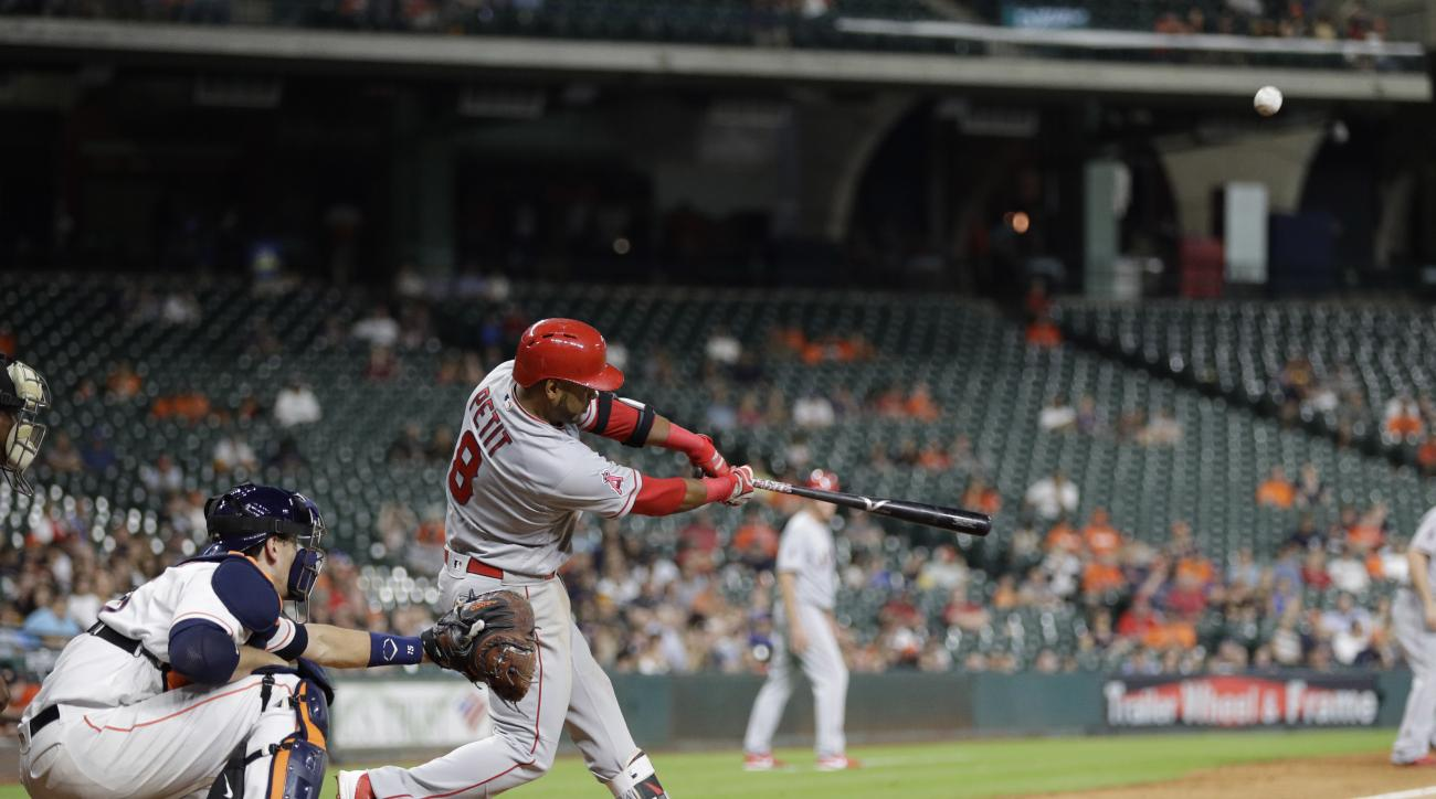 Los Angeles Angels' Gregorio Petit (8) hits a grand slam as Houston Astros catcher Jason Castro reaches for the pitch during the ninth inning of a baseball game Monday, June 20, 2016, in Houston. (AP Photo/David J. Phillip)