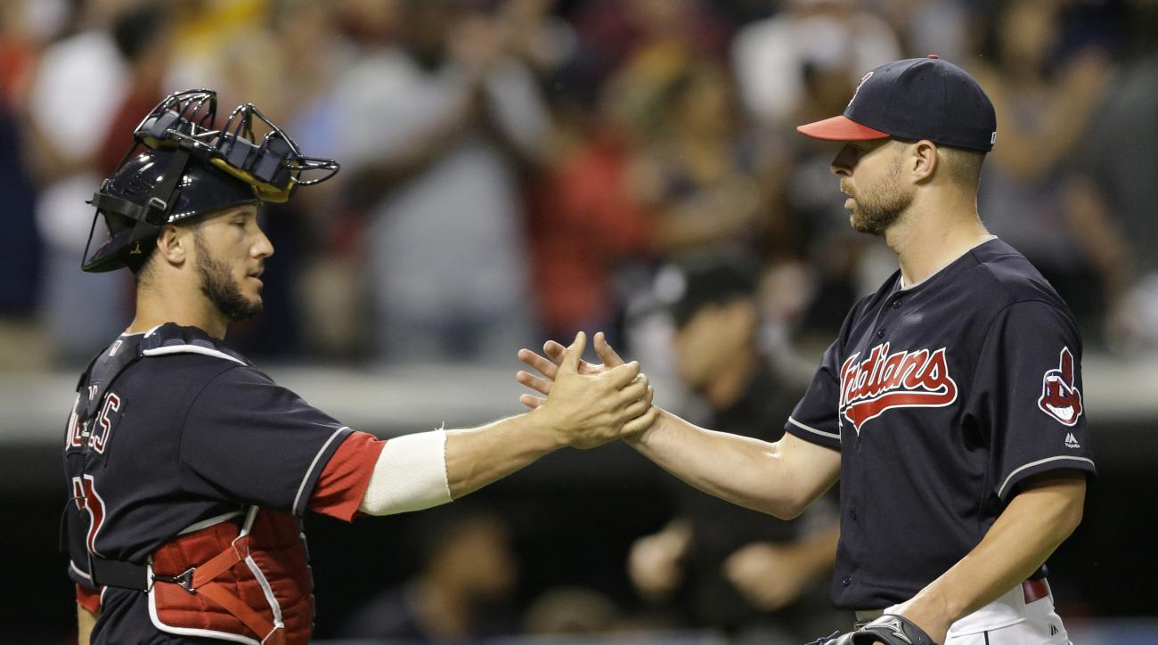 Cleveland Indians starting pitcher Corey Kluber, right, is congratulated by catcher Yan Gomes after the Indians defeated the Tampa Bay Rays 6-0 in a baseball game Tuesday, June 21, 2016, in Cleveland. Kluber had a three-hitter. (AP Photo/Tony Dejak)
