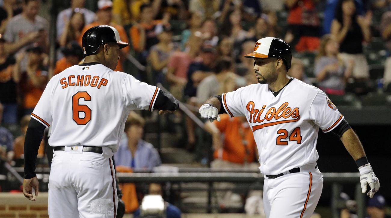Baltimore Orioles' Jonathan Schoop, left, greets teammate Pedro Alvarez at home plate after Alvarez batted him in on a home run in the fifth inning of an interleague baseball game against the San Diego Padres in Baltimore, Tuesday, June 21, 2016. (AP Phot