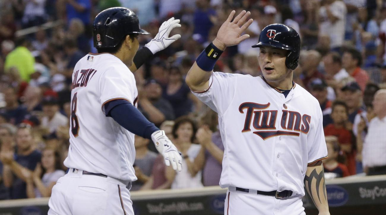 Minnesota Twins' Kurt Suzuki, left, gets a high-five from Byung Ho Park after they scored on Suzuki's two-run home run off Philadelphia Phillies relief pitcher Brett Oberholtzer during the fifth inning of a baseball game Tuesday, June 21, 2016, in Minneap