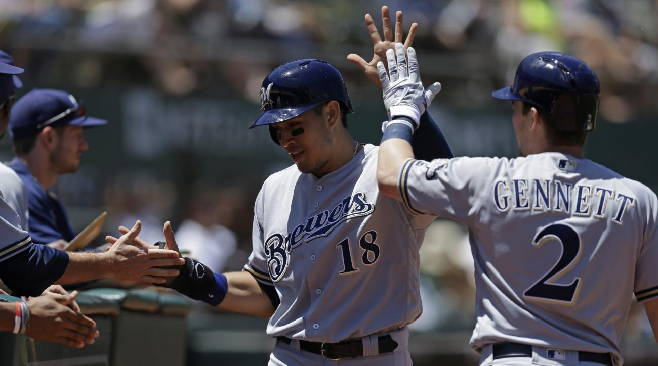 Milwaukee Brewers' Ramon Flores (18) is congratulated by Scooter Gennett, right, after scoring against the Oakland Athletics in the fifth inning of a baseball game Wednesday, June 22, 2016, in Oakland, Calif. Flores scored when Brewers' Yadiel Rivera sacr