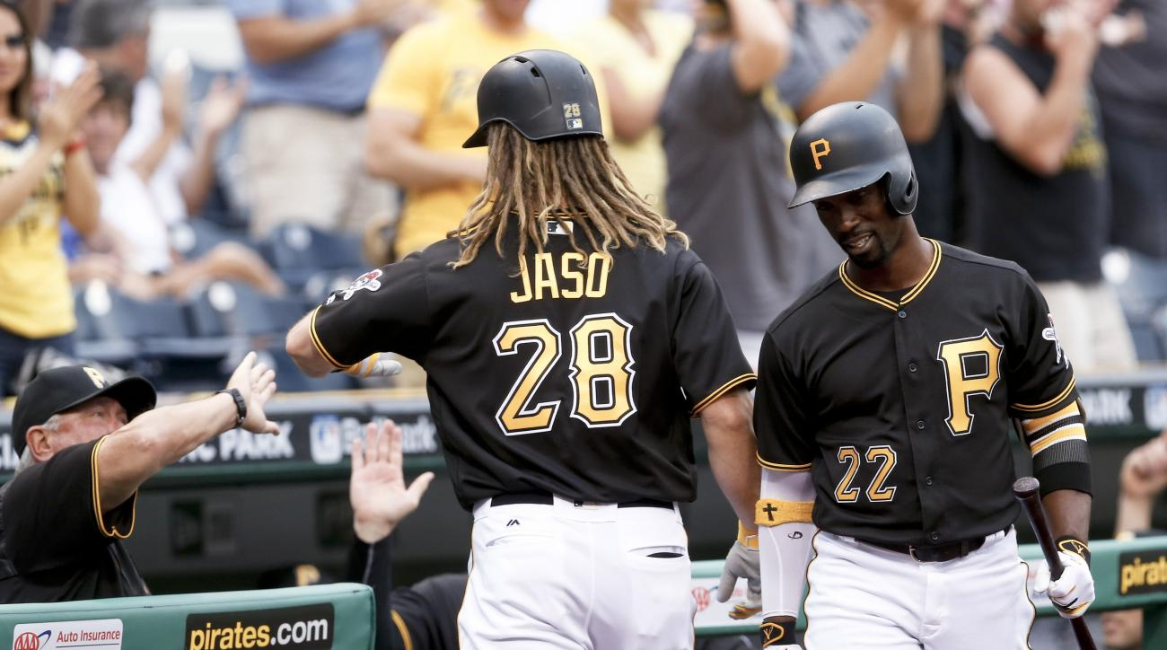 Pittsburgh Pirates' John Jaso (28) passes Andrew McCutchen (22) on his way to the dugout and is greeted by manager Clint Hurdle, left after hitting a solo home run during the first inning of a baseball game against the San Francisco Giants, Wednesday, Jun