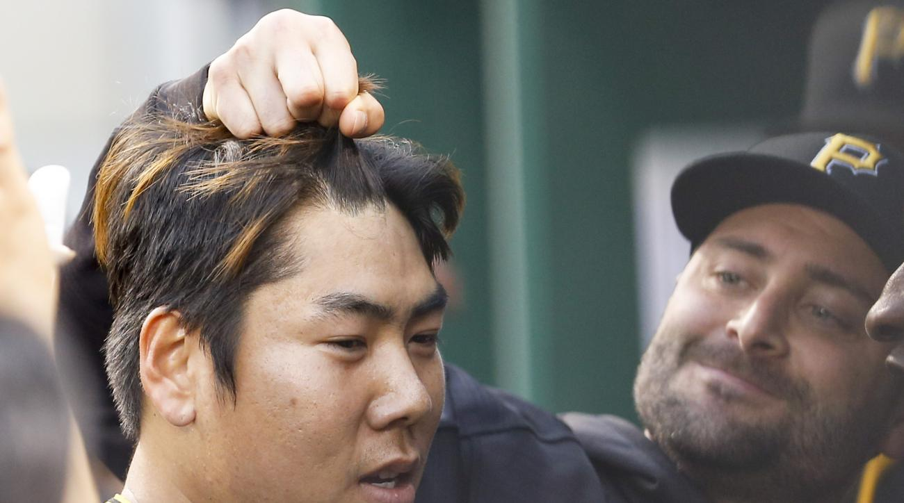 Pittsburgh Pirates' Jung Ho Kang, left. gets his hair pulled by Francisco Cervelli in the dugout as the team celebrates Kang's home run against the San Francisco Giants during the third inning of a baseball game, Wednesday, June 22, 2016, in Pittsburgh. (