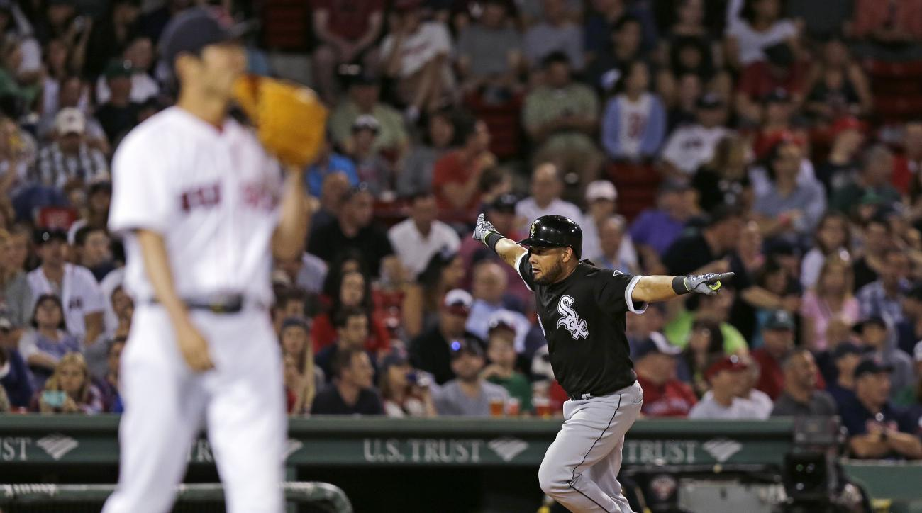 Chicago White Sox's Melky Cabrera, right, spreads his arms as he celebrates while rounding third on a two-run home run off Boston Red Sox relief pitcher Koji Uehara, left, during the eighth inning of a baseball game at Fenway Park, Wednesday, June 22, 201