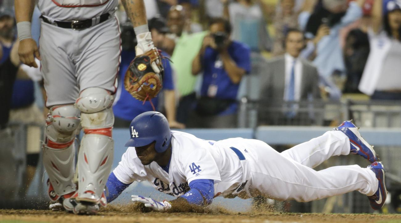 Los Angeles Dodgers' Yasiel Puig, scores game winning inside the park home run during the ninth inning of a baseball game against the Washington Nationals in Los Angeles, Wednesday, June 22, 2016. (AP Photo/Chris Carlson)
