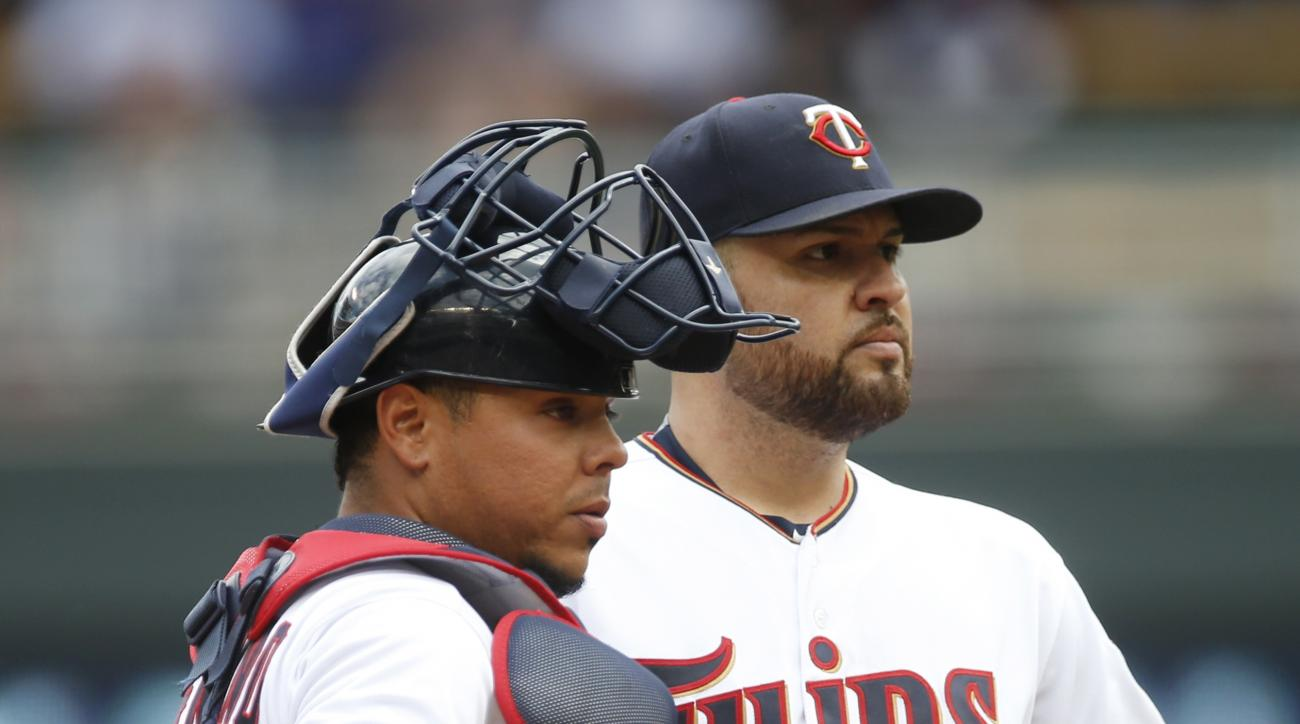 Minnesota Twins pitcher Ricky Nolasco, right, and catcher Juan Centeno wait to see if a replay will be requested in the fifth inning of a baseball game against the Philadelphia Phillies, Thursday, June 23, 2016, in Minneapolis. (AP Photo/Jim Mone)