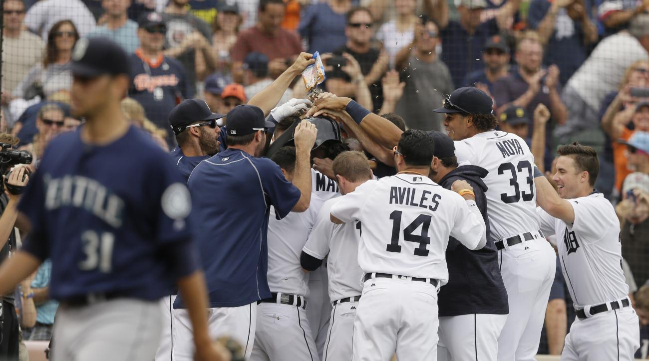 Seattle Mariners relief pitcher Steve Cishek (31) walks away as Detroit Tigers pinch runner Cameron Maybin is mobbed by teammates after scoring from third on a wild pitch during the 10th inning of a baseball game, Thursday, June 23, 2016, in Detroit. (AP