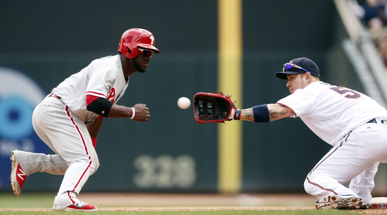 Minnesota Twins first baseman Byung Ho Park, right, of South Korea, reaches for the ball before tagging out Philadelphia Phillies' Odubel Herrera on a pickoff in the forth inning of a baseball game Thursday, June 23, 2016, in Minneapolis. (AP Photo/Jim Mo