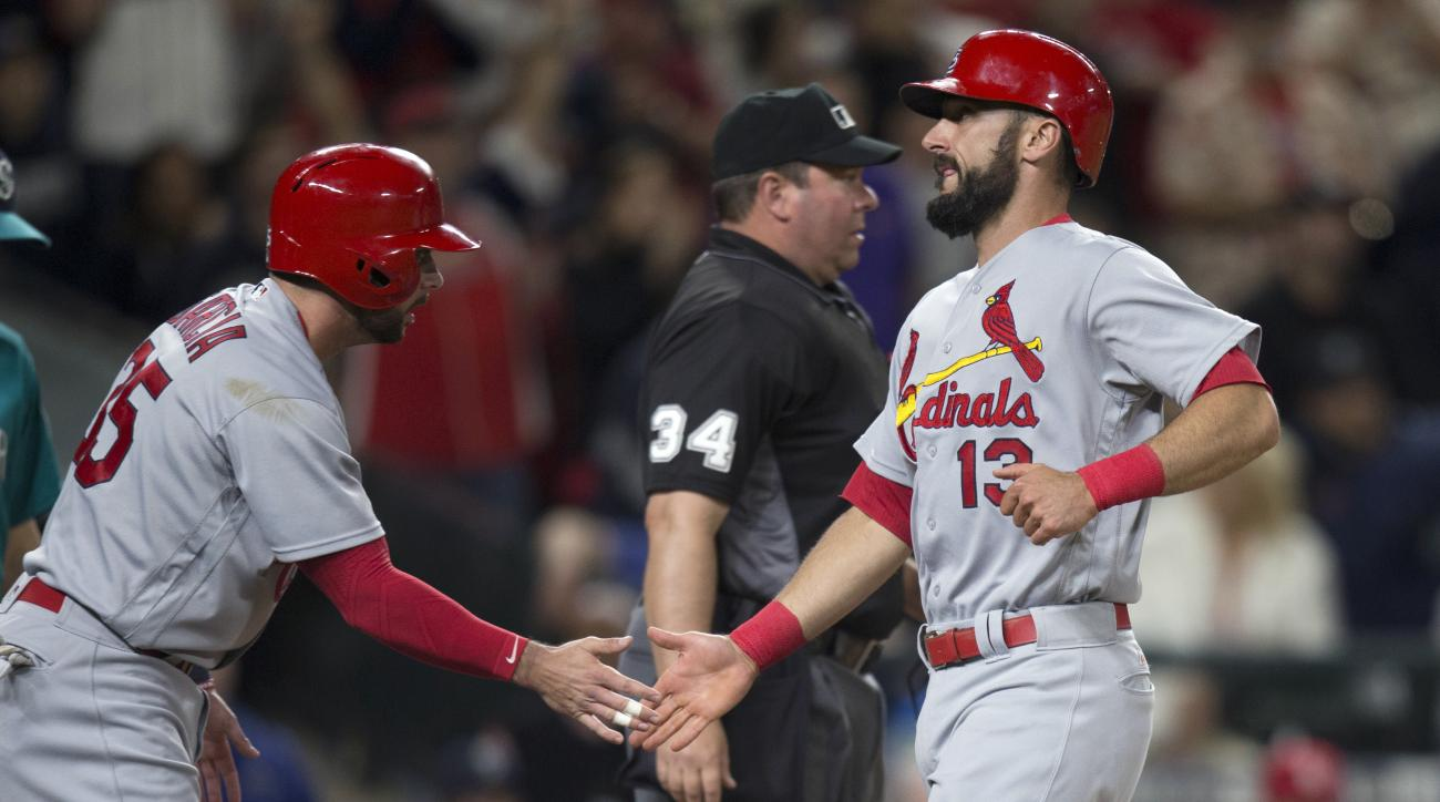 St. Louis Cardinals' Greg Garcia, left, congratulates teammate Matt Carpenter after Carpenter and Garcia scored on a bases-loaded single by Matt Holliday during the eighth inning of a baseball game against the Seattle Mariners on Friday, June 24, 2016, in