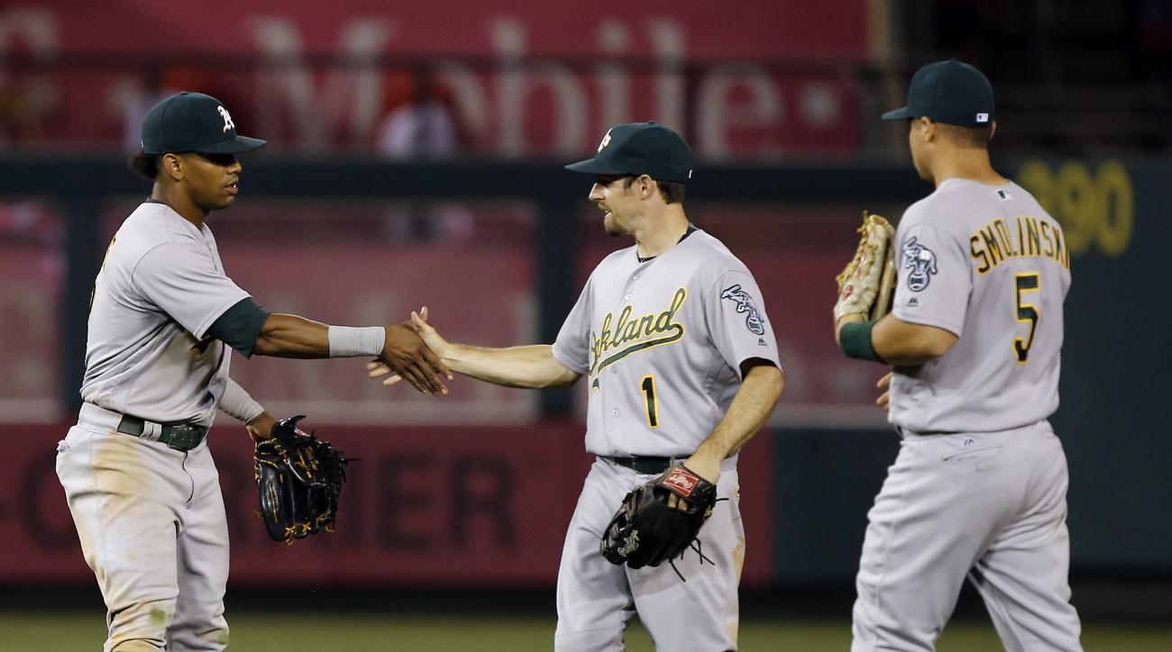 Oakland Athletics left fielder Khris Davis, left, congratulates center fielder Billy Burns, center, and right fielder Jake Smolinski, right, after the Athletics defeated the Los Angeles Angels 7-4 in a baseball game in Anaheim, Calif., Friday, June 24, 20
