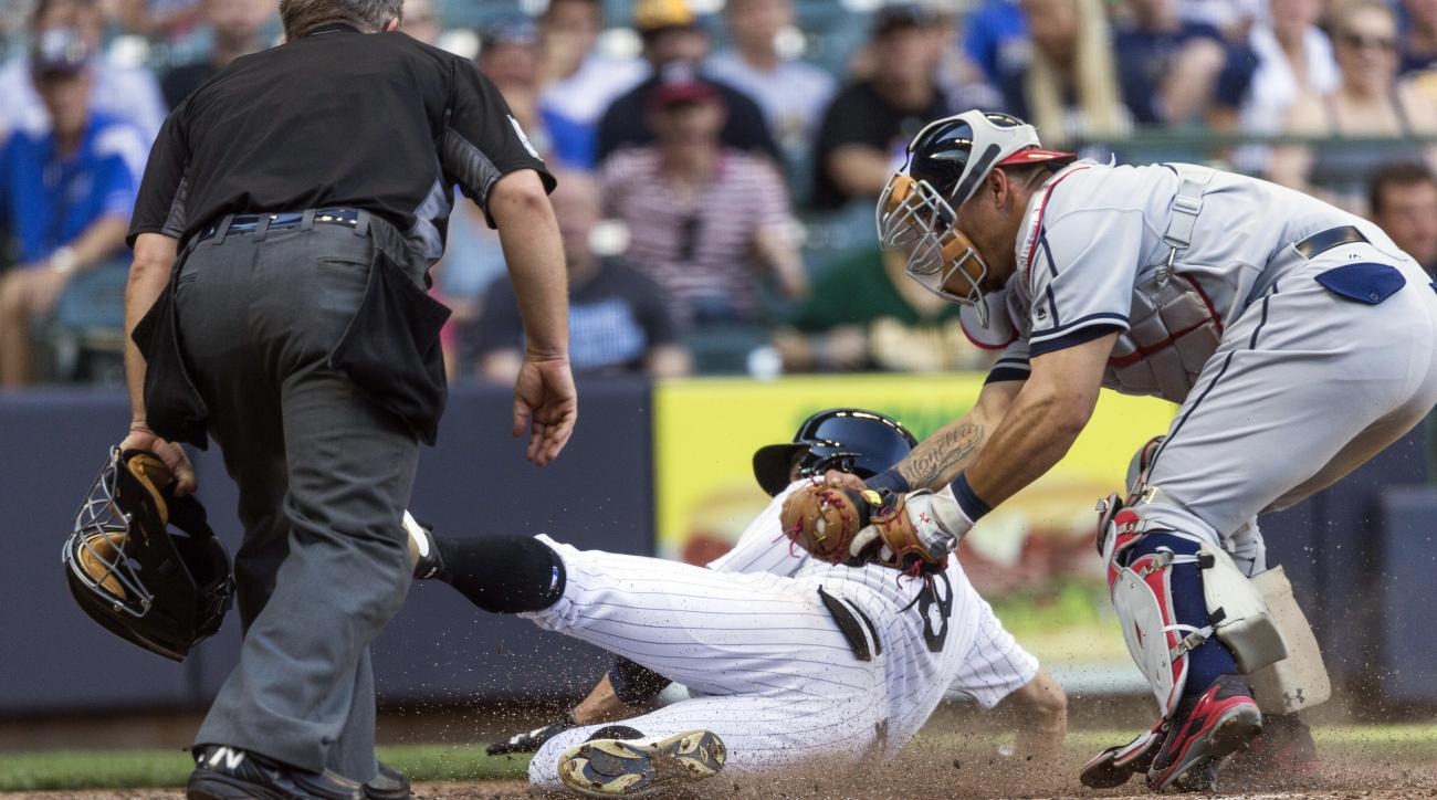 Milwaukee Brewers' Ryan Braun is tagged out at home by Washington Nationals' Wilson Ramos as home plate ump Greg Gibson looks on during the seventh inning of a baseball game Saturday, June 25, 2016, in Milwaukee. (AP Photo/Tom Lynn)