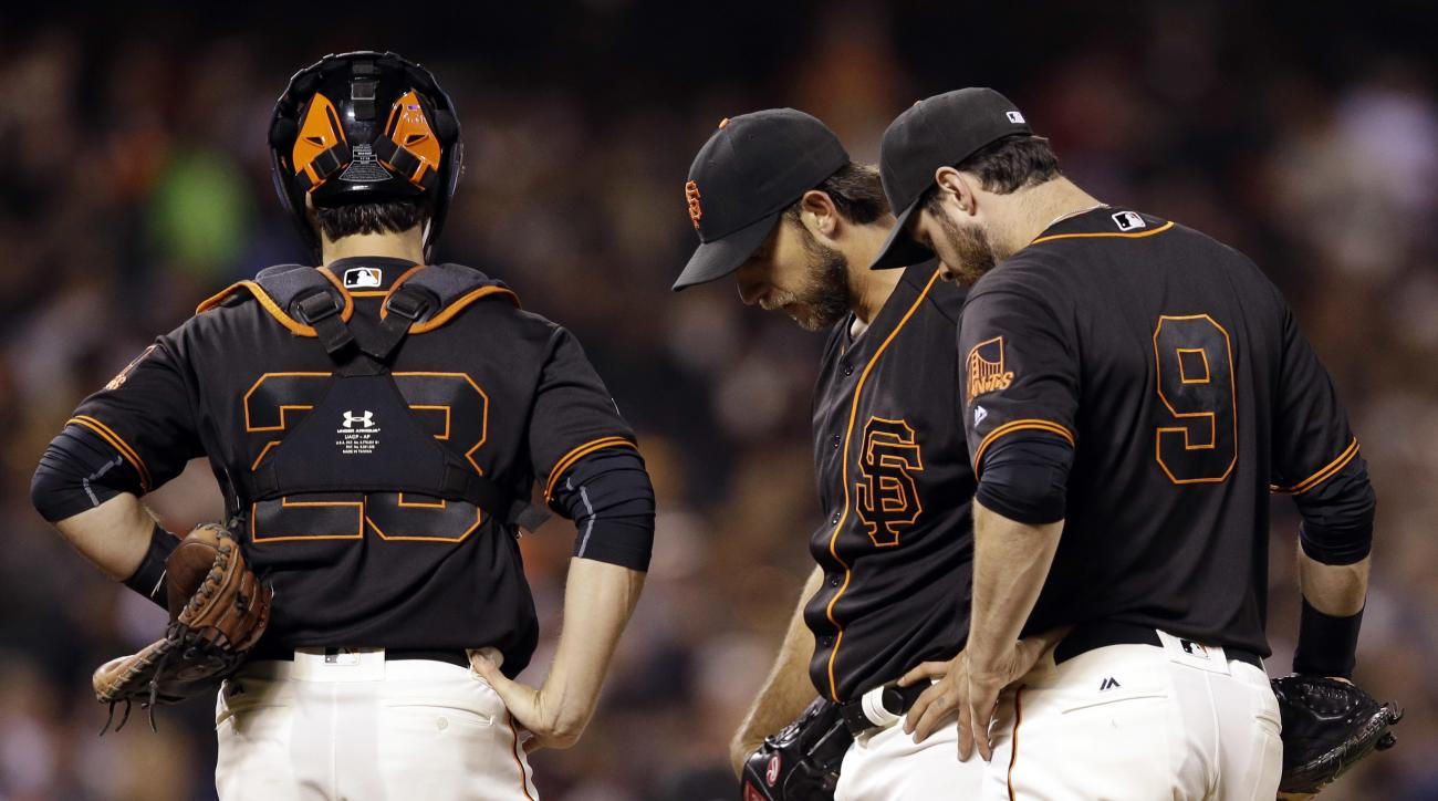 San Francisco Giants starting pitcher Madison Bumgarner, center, stands on the mound as he waits to be pulled from the name next to teammates Buster Posey, left, and Brandon Belt (9) during the seventh inning of a baseball game against the Philadelphia Ph
