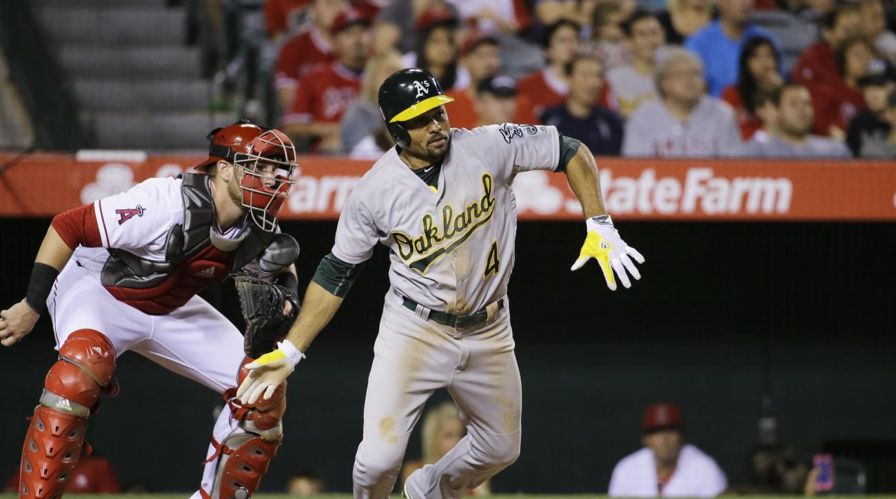 Oakland Athletics' Coco Crisp watches his two-RBI single as Los Angeles Angels catcher Jett Bandy, left, looks on during the sixth inning of a baseball game Saturday, June 25, 2016, in Anaheim, Calif. (AP Photo/Gregory Bull)