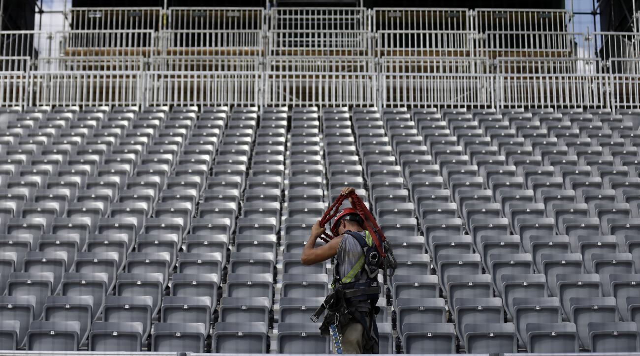 In this photo taken Thursday, June 16, 2016, a worker finishes up installing seats behind home plate as work continues on a baseball field installation on post at Fort Bragg, N.C. The Atlanta Braves and Miami Marlins will play a salute-the-troops game at