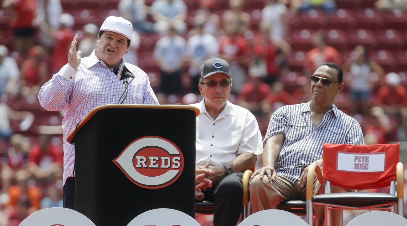 Former Cincinnati Reds player Pete Rose, left, speaks alongside Reds greats Johnny Bench, center, and Tony Perez during a ceremony to retire his No. 14 before a baseball game against the San Diego Padres, Sunday, June 26, 2016, in Cincinnati. (AP Photo/Jo