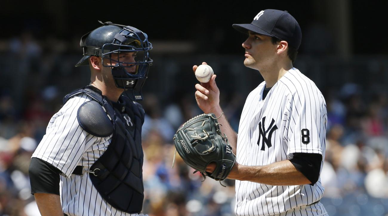 New York Yankees catcher Brian McCann, left, stands on the mound with starting pitcher Nathan Eovaldi (30) after Eovaldi allowed a two-run home run to Minnesota Twins' Brian Dozier  during the sixth inning of a baseball game in New York, Sunday, June 26,