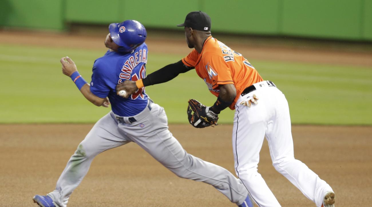 Chicago Cubs' Willson Contreras, left, is tagged out by Miami Marlins shortstop Adeiny Hechavarria on an attempt to steal second during the fourth inning of a baseball game, Sunday, June 26, 2016, in Miami. (AP Photo/Lynne Sladky)