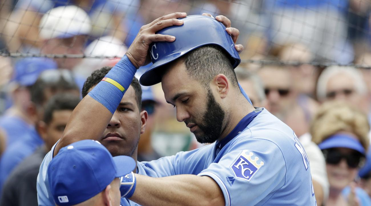 Kansas City Royals Salvador Perez. left, removes Kendrys Morales' helmet after Morales' home run in the fourth inning of a baseball game against the Houston Astros at Kauffman Stadium in Kansas City, Mo., Sunday, June 26, 2016. (AP Photo/Colin E. Braley)