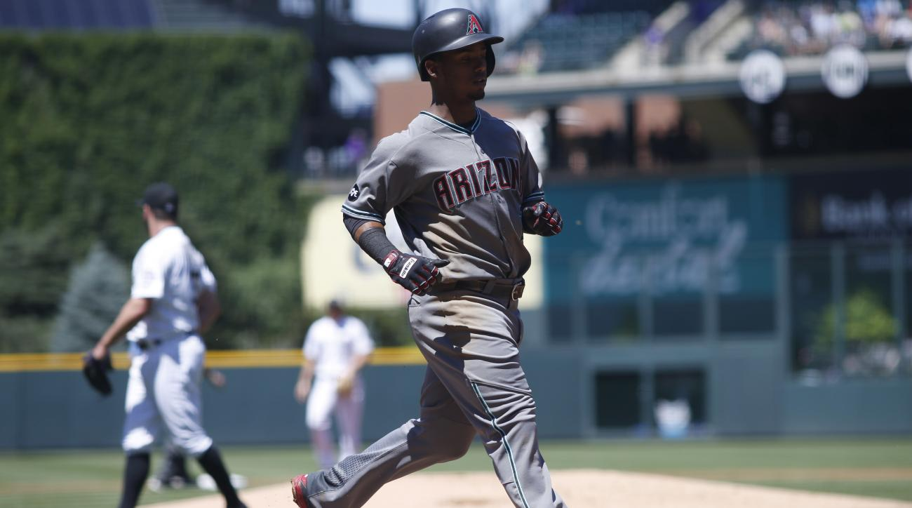 Arizona Diamondbacks' Jean Segura scores on a single hit by Paul Goldschmidt off Colorado Rockies starting pitcher Chad Bettis in the first inning of a baseball game Sunday, June 26, 2016, in Denver. (AP Photo/David Zalubowski)
