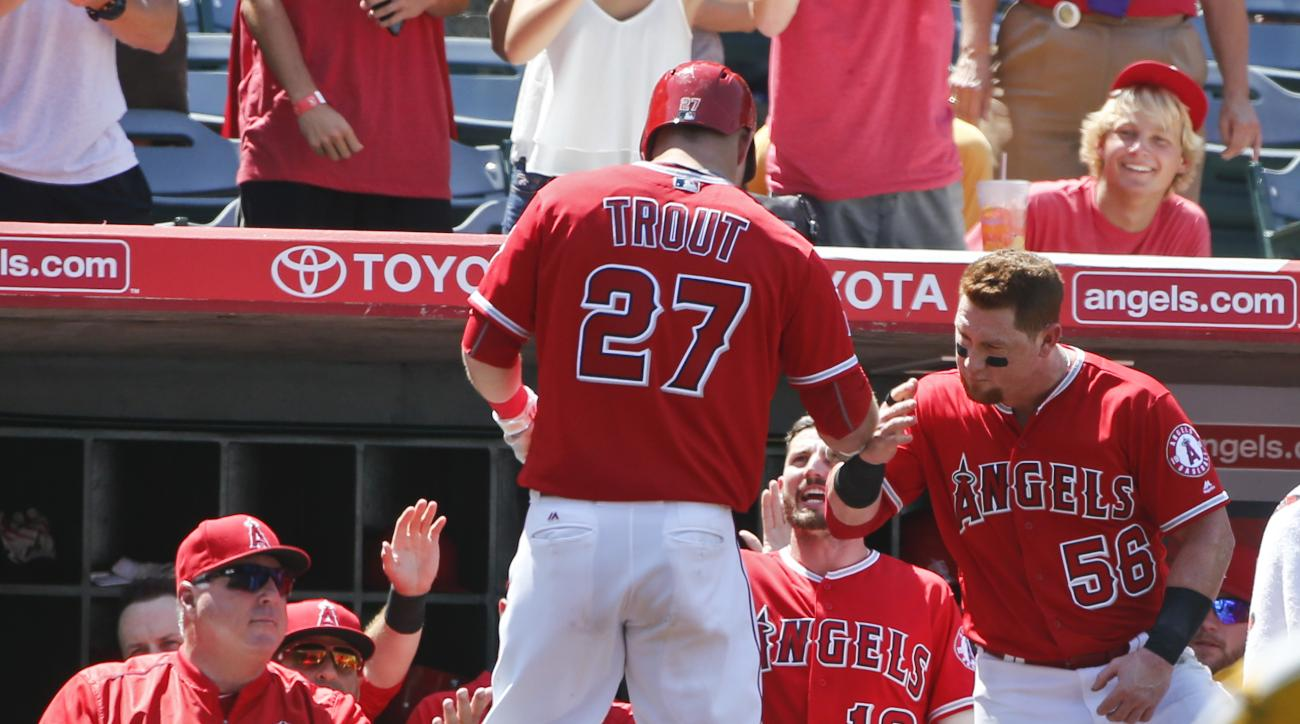 Los Angeles Angels' Mike Trout is greeted at the dugout after hitting a two-run homer against the Oakland Athletics in the seventh inning of a baseball game Sunday, June 26, 2016, in Anaheim, Calif. (AP Photo/Lenny Ignelzi)