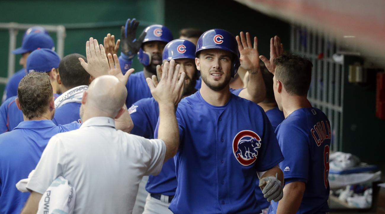 Chicago Cubs' Kris Bryant celebrates in the dugout after hitting a go-ahead three-run home run off Cincinnati Reds starting pitcher Dan Straily in the fourth inning of a baseball game, Monday, June 27, 2016, in Cincinnati. (AP Photo/John Minchillo)