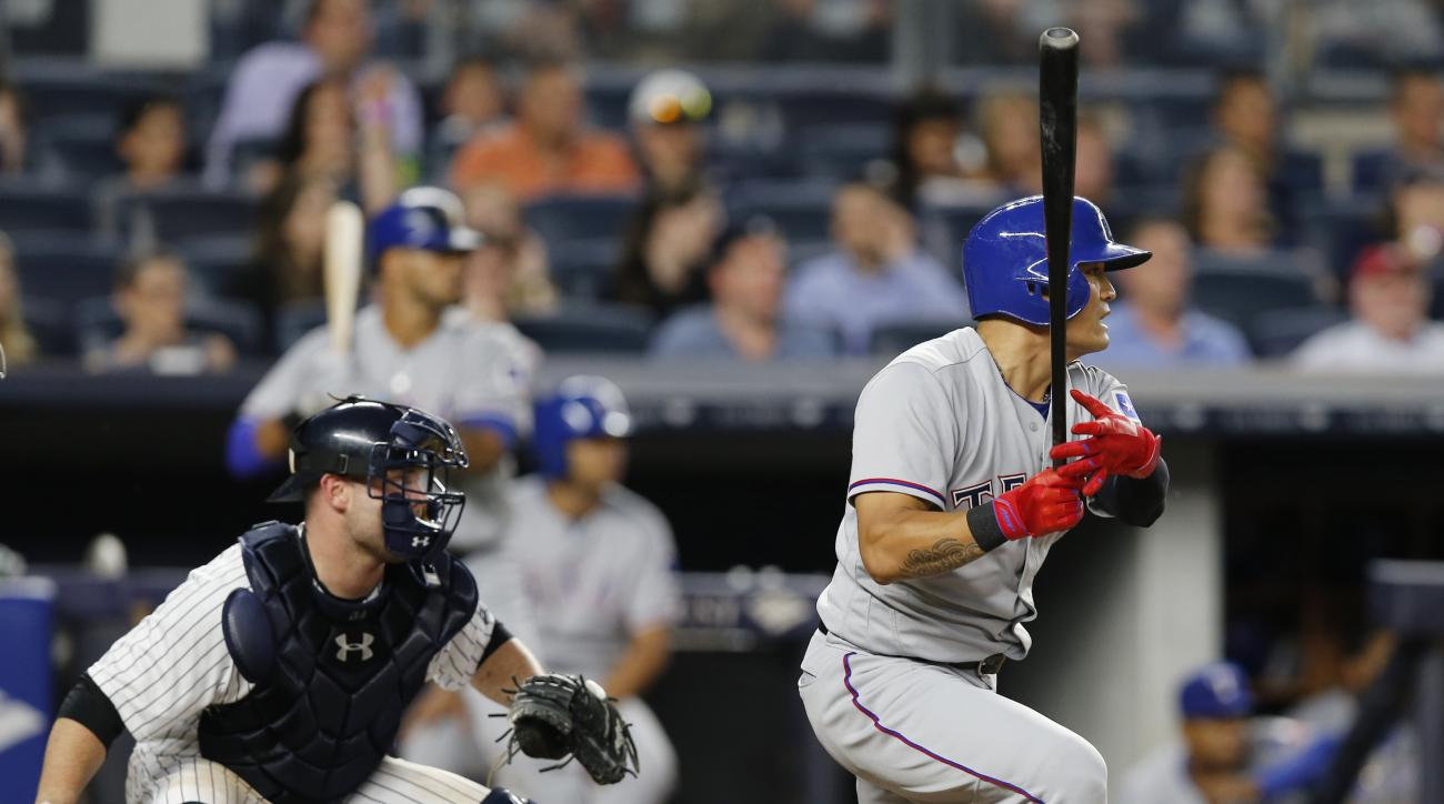 Texas Rangers Shin-Soo Choo hits a fourth-inning, two-run single during a baseball game against the New York Yankees in New York, Monday, June 27, 2016. New York Yankees catcher Brian McCann watches from behind the plate, left. (AP Photo/Kathy Willens)