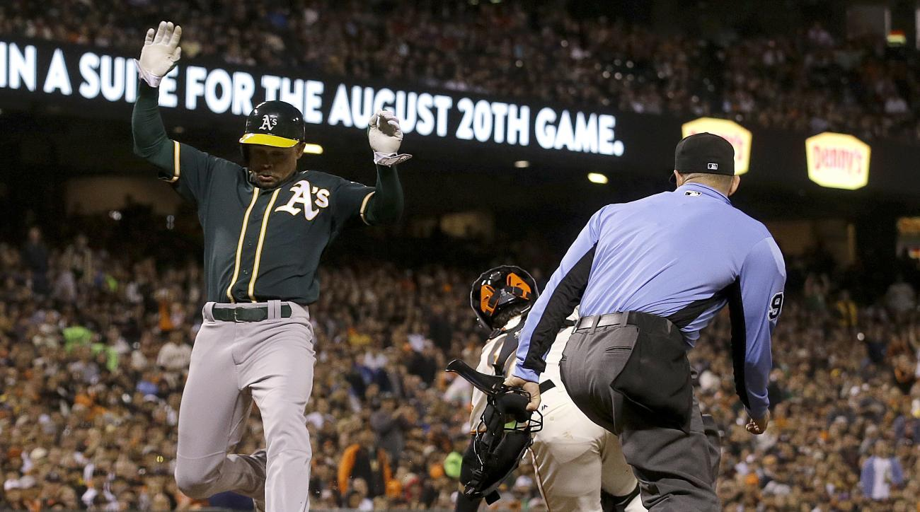 Oakland Athletics' Coco Crisp, left, scores past San Francisco Giants catcher Buster Posey as umpire Will Little watches during the seventh inning of an interleague baseball game in San Francisco, Monday, June 27, 2016. (AP Photo/Jeff Chiu)