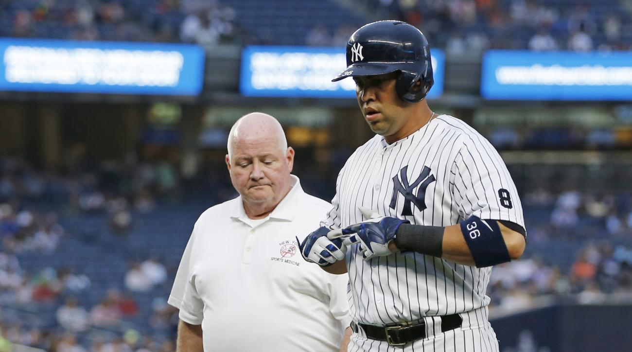 New York Yankees' Carlos Beltran, right, leaves the game with trainer Steve Donohue after an injury while running to first base on a single during the first inning of a baseball game against the Texas Rangers, in New York, Tuesday, June 28, 2016. (AP Phot