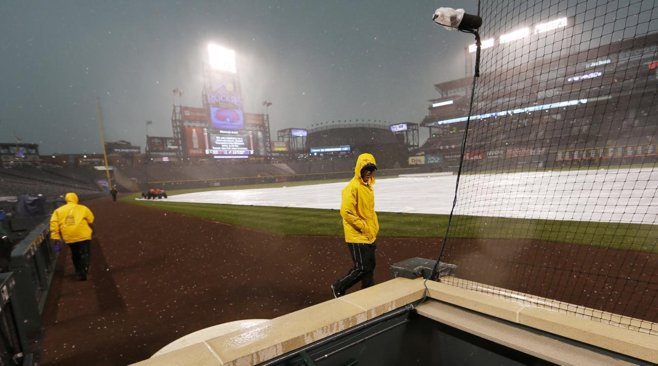 Field guards run for cover as heavy rains and hail pelt the infield of Coors Field before a baseball game between the Toronto Blue Jays and the Colorado Rockies on Tuesday, June 28, 2016, in Denver. (AP Photo/David Zalubowski)